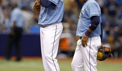 Tampa Bay Rays relief pitcher C.J. Riefenhauser and Yunel Escobar react after walking New York Yankees' Dean Anna and forcing in the go-ahead run during the 12th inning of a baseball game on Sunday, April 20, 2014, in St. Petersburg, Fla. The Yankees won 5-1. (AP Photo/Mike Carlson)