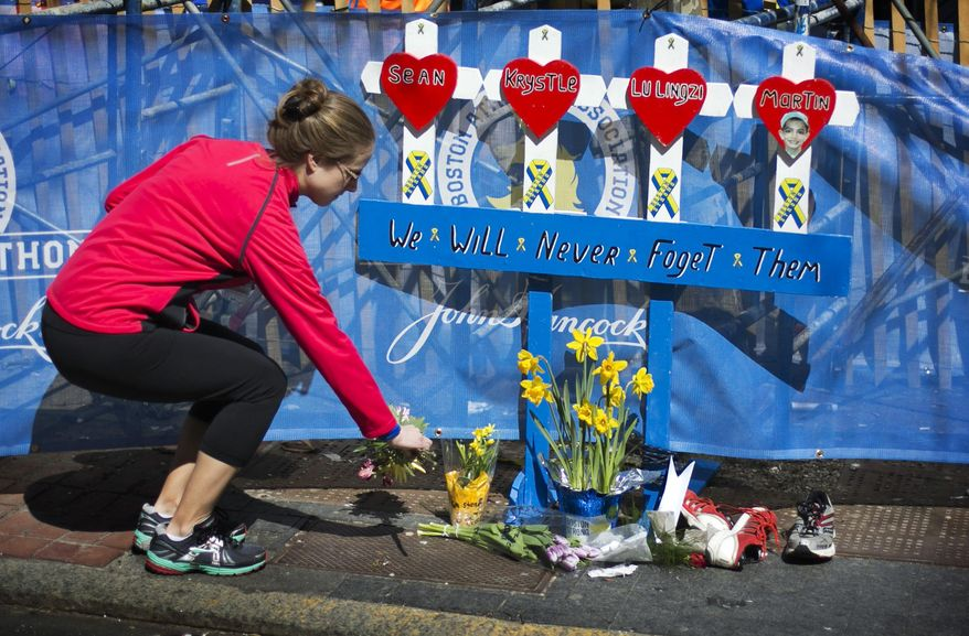Boston Marathon runner Jessica Boucher, of Arlington, Va., places flowers at a memorial honoring the victims of the 2013 Boston Marathon bombings, Sunday, April 20, 2014, in Boston. The memorial is where the first explosion happened last year near the finish line. (AP Photo/Robert F. Bukaty)