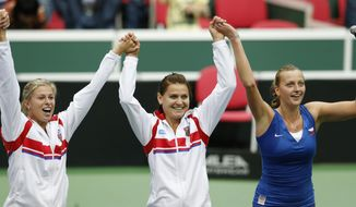 Czech Republic's Petra Kvitova, right, celebrates with her teammates Lucie Safarova, center, and Andrea Hlavackova, left, after defeating Italy's Roberta Vinci in their Fed Cup semifinal tennis match in Ostrava, Czech Republic, Sunday, April 20, 2014. Kvitova won the match and gave Czech Republic a decisive 3-0 lead. (AP Photo/Petr David Josek)