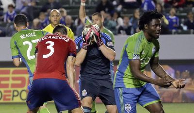 Chivas USA goalkeeper Dan Kennedy, middle, reacts with Carlos Bocanegra (3) as Seattle Sounders FC forward Obafemi Martins, right, celebrates Lamar Neagle's goal during first half a MLS soccer match Saturday, April 19, 2014, in Carson, Calif. (AP Photo/Chris Carlson)
