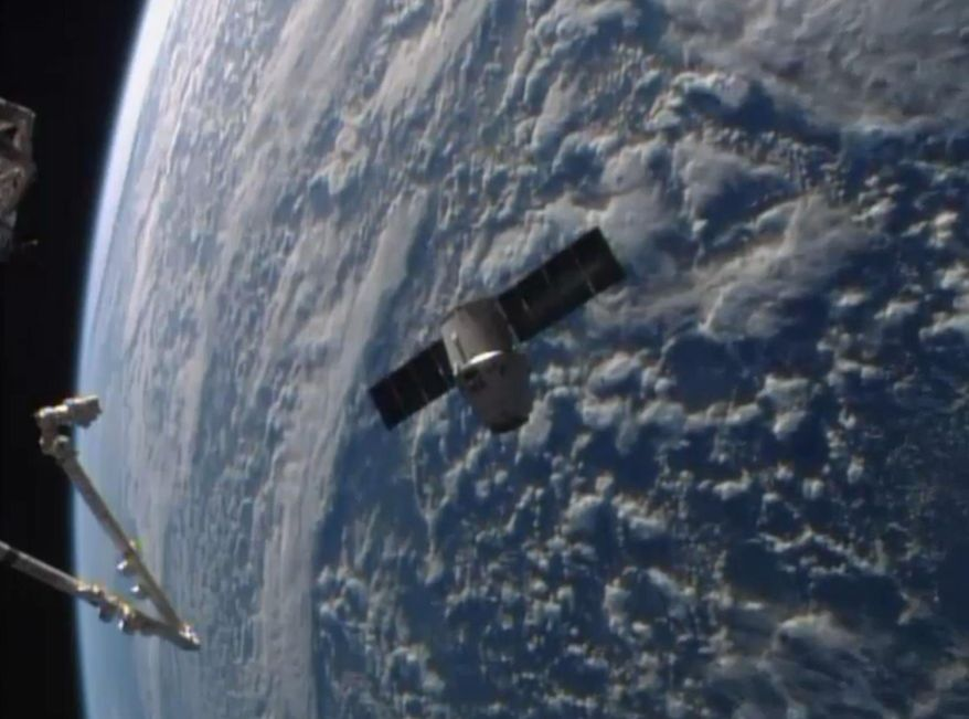 This frame grabbed image from NASA-TV Sunday April 20, 2014 shows the SpaceX Dragon resupply capsule approaching the International Space Station. It is expected to be captured by the Canadarm2, left, from the International Space Station later this morning. The pair at the time of this frame grab are traveling over the southern Atlantic Ocean.  (AP Photo/NASA-TV)