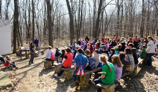 Rachel Taras, education specialist, Hawk Mountain Sanctuary, talks to the crowd about raptor nests and eggs before the annual Raptor Egg Hunt in the area of the Outdoor Amphitheater at Hawk Mountain in Kempton, Pa., Saturday, April 19, 2014. Children searched for hidden wooden raptor eggs in a non-traditional and non-competitive egg hunt. Hawk Mountain Sanctuary is home to the world's largest member-supported raptor conservation organization. (AP Photo/The Republican-Herald, Jacqueline Dormer)