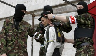A shootout at the Russia-Ukraine border between an unidentified masked man and pro-Russian activists broke a United Nations brokered truce and left at least three dead on Easter Sunday, prompting a small memorial at the scene of the skirmish. (Associated Press Photographs)
