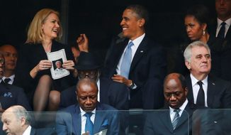 """First lady Michelle Obama, right, looks on as President Obama jokes with Danish prime minister Helle Thorning-Schmidt during former South African president Nelson Mandela's memorial service in December. Columnist Joseph Curl says Mrs. Obama can often be seen with her """"I'm-Not-Amused"""" face. (Associated Press)"""