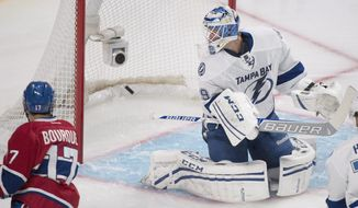 Montreal Canadiens' Rene Bourque, left, scores against Tampa Bay Lightning's goalie Anders Lindback during first period of the first round NHL Stanley Cup playoff game in Montreal, Sunday, April 20, 2014. (AP Photo/The Canadian Press, Graham Hughes)