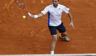 Stanislas Wawrinka of Switzerland, returns the ball to Roger Federer of Switzerland during the final match of the Monte Carlo Tennis Masters tournament in Monaco, Sunday, April 20, 2014. (AP Photo/Michel Euler)