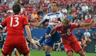 FC Dallas' Matt Hedges, center, tries to redirect a corner-kick as he is squeezed by Toronto FC's Steven Caldwell (13) and Justin Morrow, right, during an MLS soccer game on Saturday, April 19, 2014, in Frisco, Texas. (AP Photo/The Dallas Morning News, Mark M. Hancock) MANDATORY CREDIT, NO SALES, MAGAZINES OUT, TV OUT, INTERNET USE BY AP MEMBERS ONLY