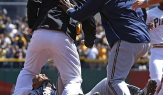 Pittsburgh Pirates' Travis Snider, left, takes down Milwaukee Brewers' Carlos Gomez, bottom, as Brewers' Rickie Weeks, right, joins a skirmish between the teams during the third inning of a baseball game in Pittsburgh, Sunday, April 20, 2014. Gomez and Snider were ejected from the game. (AP Photo/Gene J. Puskar)