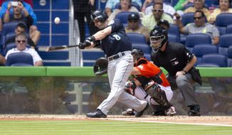 Seattle Mariners batter Willie Bloomquist hits a foul ball as Miami Marlins catcher Jeff Matthis (6) and umpire Ed Hickox watch during the third inning of a baseball game in Miami, Sunday, April 20,2014. (AP Photo/J Pat Carter)