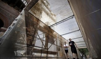 Tourists walk through the temporary structure running under the east tower of Mission San Xavier del Bac south of Tucson, Ariz., to ward off pieces that could fall from the structure, Thursday, April 16, 2014, Tucson, Ariz.  (AP Photo/ Arizona Daily Star, Kelly Presnell)