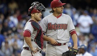 Arizona Diamondbacks starting pitcher Mike Bolsinger, right, and catcher Miguel Montero look at the scoreboard during the fifth inning of a baseball game against the Los Angeles Dodgers, Saturday, April 19, 2014, in Los Angeles. (AP Photo/Jae C. Hong)