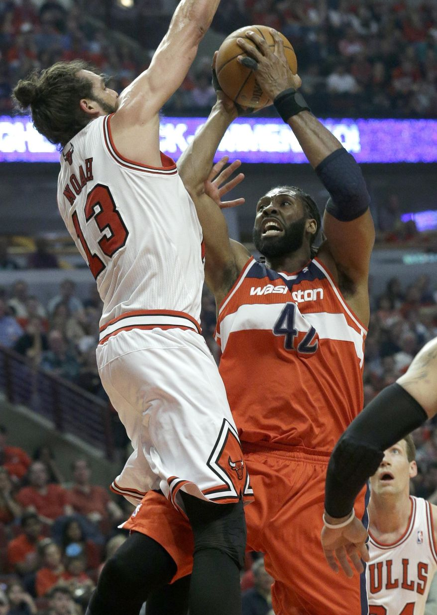 Washington Wizards forward Nene, right, drives to the basket against Chicago Bulls center Joakim Noah during the first half in Game 1 of an opening-round NBA basketball playoff series in Chicago, Sunday, April 20, 2014. (AP Photo/Nam Y. Huh)