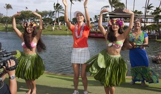 Michelle Wie, center, dances the hula after winning the 2014 LPGA LOTTE Championship golf tournament at Ko Olina Golf Club, Saturday, April 19, 2014, in Kapolei, Hawaii. (AP Photo/Eugene Tanner)