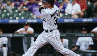Colorado Rockies' Justin Morneau follows the flight of his two-run home run against the Philadelphia Phillies in the seventh inning of the Phillies' 10-9 victory in a baseball game in Denver on Sunday, April 20, 2014. (AP Photo/David Zalubowski)