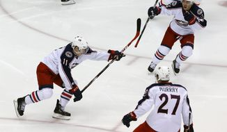 Columbus Blue Jackets' Matt Calvert (11) celebrates his game-winning goal with teammates Ryan Murray (27), and Cam Atkinson (13) in the second overtime period of a first-round NHL playoff hockey game in Pittsburgh Saturday, April 19, 2014. The Blue Jackets won 4-3, to even the series at 1-1. (AP Photo/Gene J. Puskar)