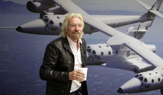 FILE - This Sept. 25, 2013 file photo shows British entrepreneur Richard Branson at the Virgin Galactic hangar at Mojave Air and Space Port in Mojave, Calif. One lucky citizen of the oil-rich United Arab Emirates could soon get the chance to be rocketed into space. Government-backed Aabar Investments on Sunday announced the start of a competition to award an Emirati a free spot aboard Virgin Galactic's spaceship when it begins ferrying space tourists briefly into space. (AP Photo/Reed Saxon, File)