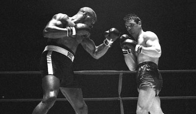 "FILE - In this Feb. 23, 1965 file photo, Rubin ""Hurricane"" Carter, left, knocks out Italian boxer Fabio Bettini in the 10th and last round of their fight at the Falais Des Sports in Paris. Carter, who spent almost 20 years in jail after twice being convicted of a triple murder he denied committing, died at his home in Toronto, Sunday, April 20, 2014, according to long-time friend and co-accused John Artis. He was 76. (AP Photo/File)"