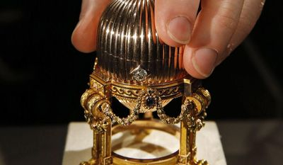 A jeweler's employee holding a Faberge Egg, one of the eight missing Faberge imperial eggs that was found at a flea market in the American Midwest, poses for photographers in central London, Monday, April 7, 2014. It was originally given by Tsar Alexander III to his wife Empress Maria Feodorovna for Easter 1887. A London antique dealer said that a scrap metal entrepreneur bought the egg for about 14,000 US dollars, thinking he could make a small profit by reselling the piece for its gold content. It turned out the jewel-encrusted piece was worth millions. Both buyer and seller want to remain anonymous, and did not disclose the sale price — but experts note that a non-imperial Faberge egg sold at Christie's for 18.5 million US dollars in 2007. Only 50 of the imperial eggs were made for the royal family, and eight remained missing before the latest find, though only three of those are known to have survived the Russian revolution. It will be on display at Wartski's London showroom April 14-17, the first time it will have been seen in public for 112 years. (AP Photo/Lefteris Pitarakis)