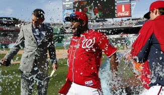 Washington Nationals' Denard Span, center, is doused by relief pitcher Tyler Clippard, right, with MASN broadcast reporter Dan Kolko, left, nearby after a baseball game against the St. Louis Cardinals at Nationals Park, Sunday, April 20, 2014, in Washington. Span hit a game-winning sacrifice fly for the Nationals' 3-2 victory. (AP Photo/Alex Brandon)