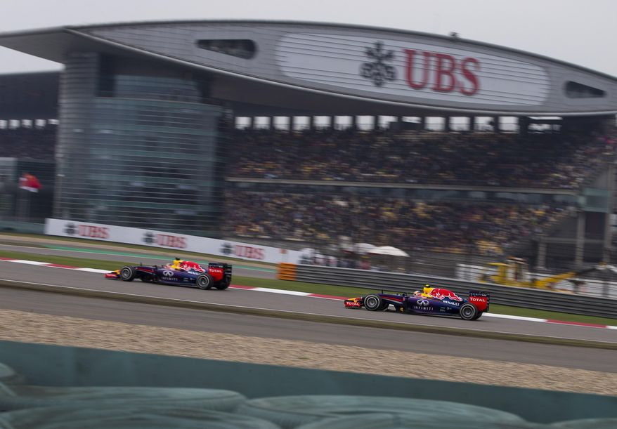 Red Bull Racing driver Sebastian Vettel of Germany, left, and his teammate Daniel Ricciardo of Australia drive past the grand stand during the Chinese Formula One Grand Prix at Shanghai International Circuit in Shanghai, China Sunday, April 20, 2014. (AP Photo/Andy Wong)