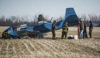 In this April 19, 2014 photo, police, firemen and medical personnel respond to a plane crash in Shiawassee County's Venice Township, Mich. The Flint Journal says Saturday afternoon's crash killed 63-year-old Richard K. Hayward of Vassar and 49-year-old Mark J. Kozan of Caro. (AP Photo/The Flint Journal, Katie McLean)