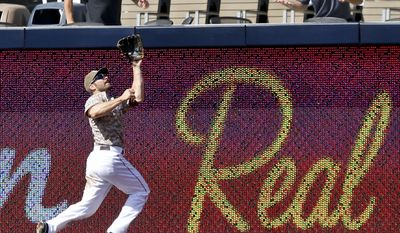 San Diego Padres right fielder Xavier Nady jumps at the fence to make the catch on a long drive hit by San Francisco Giants' Gregor Blanco in the eighth inning of a baseball game Sunday, April 20, 2014, in San Diego.  (AP Photo/Lenny Ignelzi)