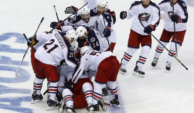 Columbus Blue Jackets' Matt Calvert (11) is congratulated by teammates after scoring his game-winning goal in the second overtime period of a first-round NHL playoff hockey game against the Pittsburgh Penguins in Pittsburgh, Saturday, April 19, 2014. The Blue Jackets won 4-3, to even the series at 1-1. (AP Photo/Gene J. Puskar)