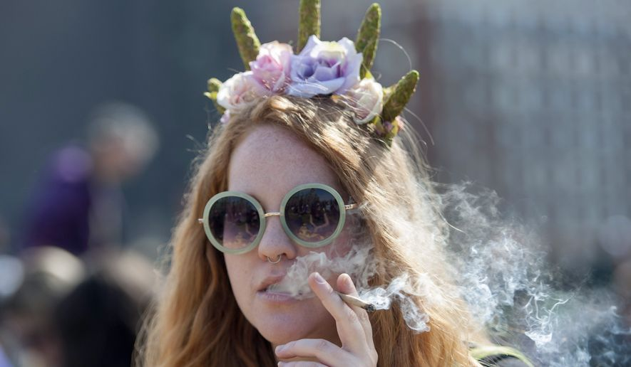 A woman smokes a joint at the Fill the Hill marijuana rally on Parliament Hill in Ottawa on Sunday, April 20, 2014. (AP Photo/The Canadian Press, Justin Tang)
