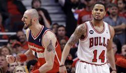 Washington Wizards center Marcin Gortat, left, reacts after scoring a basket as Chicago Bulls guard D.J. Augustin reacts during the second half in Game 1 of an opening-round NBA basketball playoff series in Chicago, Sunday, April 20, 2014. The Wizards won 102-93. (AP Photo/Nam Y. Huh)