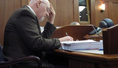 In this April 20, 2014 photo, Rep. Alan Austerman, R-Kodiak, works at his desk on the House floor during a break in floor action in Juneau, Alaska. The House and Senate plan to reconvene later Monday to try to reach resolution on an education package. (AP Photo/Becky Bohrer)