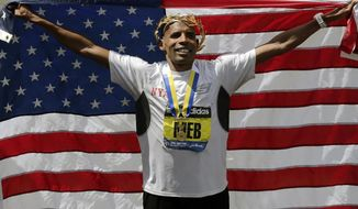 Meb Keflezighi, of San Diego, Calif., celebrates his victory with an American flag after the 118th Boston Marathon Monday, April 21, 2014 in Boston. (AP Photo/Charles Krupa)