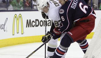 Pittsburgh Penguins' Sidney Crosby, left, and Columbus Blue Jackets' Nikita Nikitin, of Russia, fight for a loose puck during the first period of a first-round NHL playoff hockey game Monday, April 21, 2014, in Columbus, Ohio. (AP Photo/Jay LaPrete)