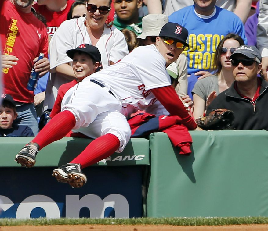Boston Red Sox third baseman Brock Holt sits on the wall after he couldn't get to a foul ball off the bat of Baltimore Orioles' Nick Markakis during the third inning of a baseball game at Fenway Park in Boston, Monday, April 21, 2014. (AP Photo/Winslow Townson)