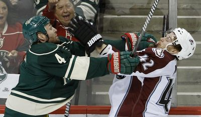 Minnesota Wild defenseman Clayton Stoner (4) shoves Colorado Avalanche center Brad Malone (42) during the first period of Game 3 of an NHL hockey first-round playoff series in St. Paul, Minn., Monday, April 21, 2014. (AP Photo/Ann Heisenfelt)