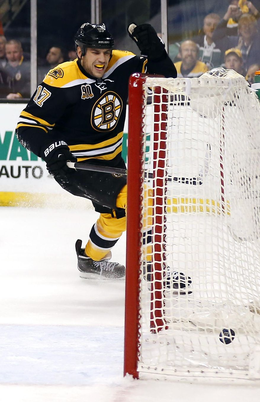 As the puck goes in the net, Boston Bruins' Milan Lucic celebrates after scoring against the Detroit Red Wings during the second period of Game 2 of a first-round NHL hockey playoff series in Boston, Sunday, April 20, 2014. (AP Photo/Winslow Townson)