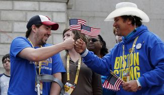 Holding American flags, Boston Marathon bombing survivor Jeff Bauman, left, bumps fists with Carlos Arredondo near the finish line of the the 118th Boston Marathon, Monday, April 21, 2014, in Boston. (AP Photo/Elise Amendola)