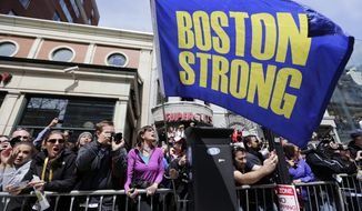 "Race fans with a ""Boston Strong"" flag cheer for competitors near the finish line of the 118th Boston Marathon, Monday, April 21, 2014, in Boston. (AP Photo/Robert F. Bukaty)"