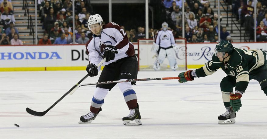 Colorado Avalanche center Nathan MacKinnon (29) passes to a teammate in front of Minnesota Wild left wing Erik Haula (56), of Finland, during the second period of Game 3 of an NHL hockey first-round playoff series in St. Paul, Minn., Monday, April 21, 2014. (AP Photo/Ann Heisenfelt)
