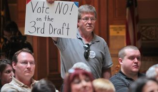 Randy Brown, from Mooresville, Ind., expresses his opinion with a sign, as he listens to speakers, during the Hoosiers Against Common Core rally at the Statehouse, Monday, April 21, 2014.  After the rally, participants walked to Government Center South to attend the Indiana Education Roundtable meeting. (AP Photo/The Indianapolis Star, Kelly Wilkinson)