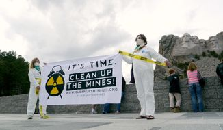 This Sunday, April 20, 2014 photo provided by Clean Up The Mines shows Dr. Margaret Flowers, left, and Helen Jaccard demonstrating for the national Clean Up The Mines effort at the Mouth Rushmore National Memorial in Keystone, S.D. The state has over 250 abandoned uranium mines. The South Dakota group Defenders of the Black Hills is working with Clean Up The Mines to educate people about the number of mines and possible health risks of uranium exposure through water and air. (AP Photo/Courtesy of Clean Up The Mines)