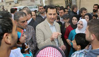 """In this photo taken on Sunday, April 20, 2014 and released by the Syrian official news agency SANA, Syrian President Bashar Assad, center, speaks with Syrian citizens during his visit to Ain al-Tineh village, near Damascus, Syria. Assad visited on Sunday a historic Christian village his forces recently captured from rebels, state media said, as the country's Greek Orthodox Patriarch vowed that Christians in the war-ravaged country """"will not submit and yield"""" to extremists. The rebels, including fighters from the al-Qaida-affiliated Nusra Front, took Maaloula several times late last year. (AP Photo/SANA)"""