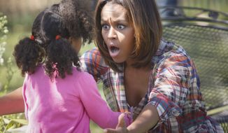 A youngster gets an enthusiastic hug from first lady Michelle Obama after she read to a group of children during the annual White House Easter Egg Roll, Monday, April 21, 2014, on the South Lawn of the White House in Washington. This year's event features live music, cooking stations, storytelling, and of course, some Easter egg rolling.(AP Photo/J. Scott Applewhite)
