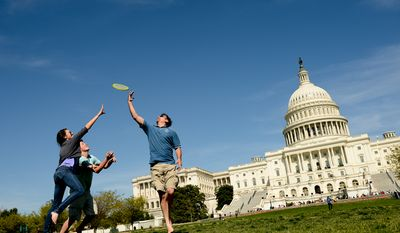 Mike Bowlin of La Plata, Md., and his his son Michael and Michael's girlfriend Alexa all try to catch a frisbee on the west lawn of the U.S. Capitol Building, Washington, D.C., Monday, April 21, 2014. (Andrew Harnik/The Washington Times)