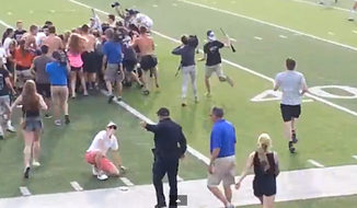 A Texas police officer is being investigated after a video showed him kicking and tripping high school students as they rushed onto the soccer field after a big win Saturday. (Rohan Gupta via YouTube)