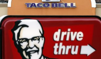 This Jan. 31, 2014 photo shows a Taco Bell facade behind a KFC drive-thru sign in Saugus, Mass. Fast-food conglomerate Yum! Brands, Inc., headquartered in Louisville, Ky., reports quarterly earnings on Tuesday, April 22, 2014. (AP Photo/Elise Amendola)