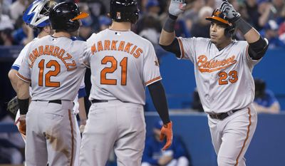 Baltimore Orioles' Nelson Cruz, right, celebrates his three-run home run with teammates Steve Lombardozzi, left, and Nick Markakis during sixth inning MLB baseball action against the Toronto Blue Jays in Toronto on Tuesday, April 22, 2014.  (AP Photo/The Canadian Press, Darren Calabrese)