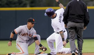 Colorado Rockies' Brandon Barnes, center, steals second base with San Francisco Giants' Ehire Adrianza covering during the first inning of a baseball game, Tuesday, April 22, 2014, in Denver. (AP Photo/Barry Gutierrez)