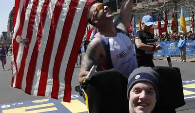 Lucas Carr, rear, celebrates after pushing Matt Brown across the finish line in the wheelchair division of the 118th Boston Marathon Monday, April 21, 2014 in Boston. (AP Photo/Elise Amendola)