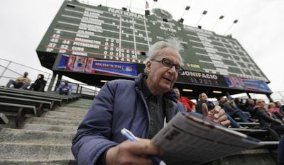 In this April 10, 2014 photo, John Weber keeps score with a pencil and scorecard as he watches a baseball game between Pittsburgh Pirates and Chicago Cubs at Wrgley Field Thursday, in Chicago. The 86-year-old retired transit worker figures he is an increasingly rare kind of baseball fan. Between batters and between pitches, most fans in the stands at Wrigley _ and everywhere else in the majors _ take their eyes off the game to peck away at smartphones, not bothering to try to figure out the baseball hieroglyphics that Weber and other purists scrawl on their cards. (AP Photo/Kiichiro Sato)