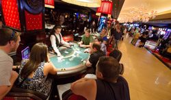 ** FILE ** This April 21, 2014, photo provided by The Cromwell shows patrons playing blackjack on the at The Cromwell Hotel and Casino as it opens for business. Slot machines are now ringing at the boutique hotel replacing Bill's Gamblin' Hall & Saloon in the heart of the Las Vegas Strip. (AP Photo/The Cromwell, Erik Kabik)